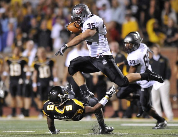 Montana's Dan Moore (35) hurdles over Appalachian State's Troy Sanders (9) on his way to the end zone during the fourth quarter of an NCAA college football game in Boone, N.C., Saturday, Sept. 8, 2012.