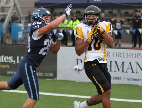 Towson's #10, Spencer Wilkins, right, hauls in a touchdown pass over Villanova's #20, Joe Sarnese during the second quarter. (Michael Bryant / Staff Photographer)