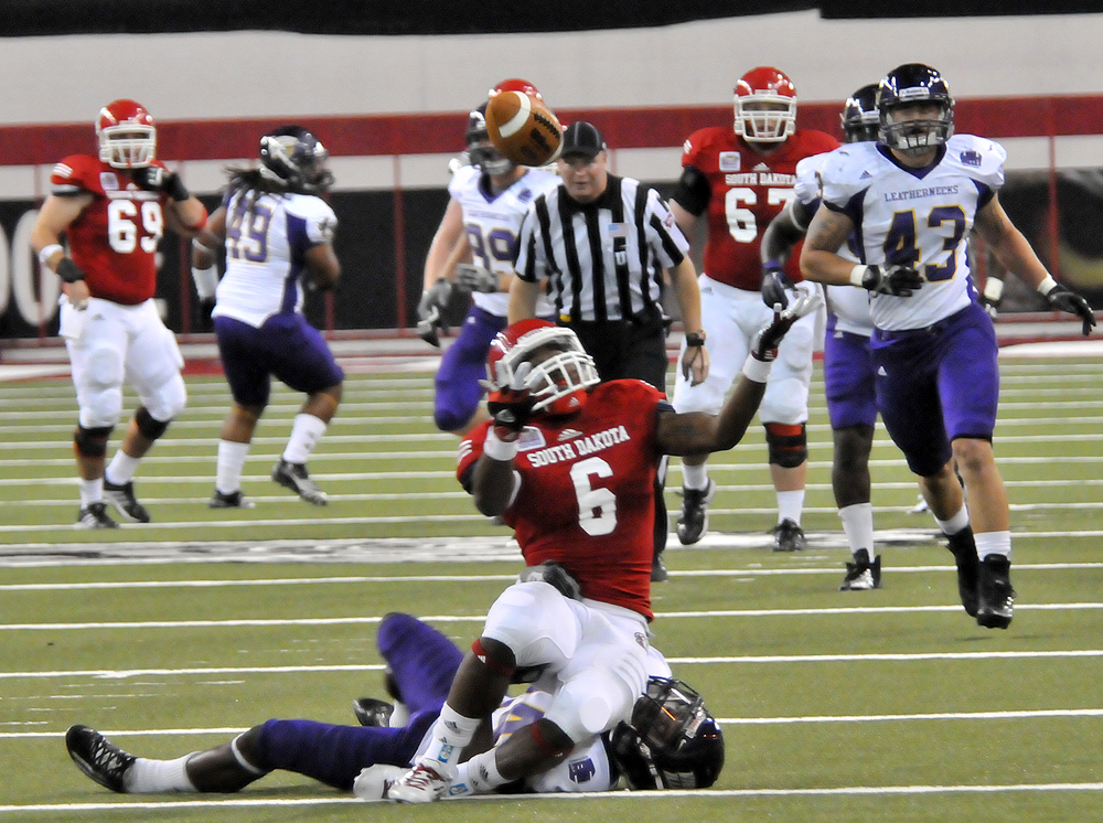 South Dakota wide receiver Terrance Terry, 6, tries to find the ball after it got tipped up as he was hit by a Western Illinois defender. The ball fell out of his reach.