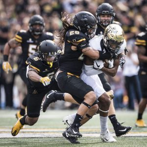 Wake Forest wide receiver Scotty Washington is tackled after a reception and run by App State linebacker Devan Stringer (28) on Saturday in Boone. (Andrew Dye/Winston-Salem Journal)